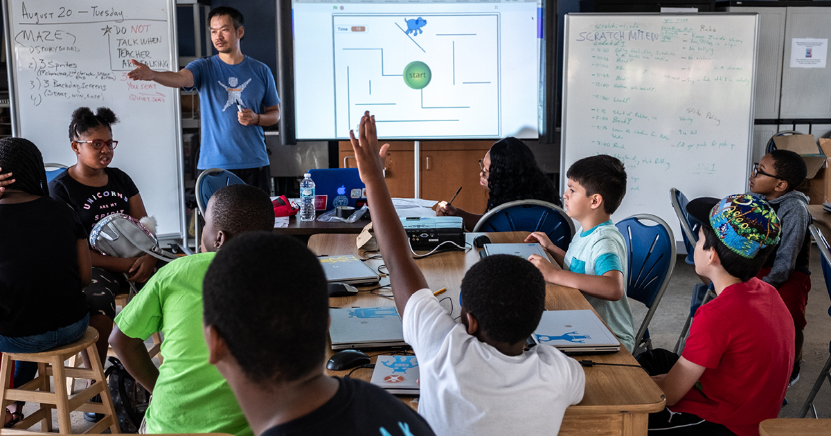 A teacher stands at the front of a classroom and digital presentation. Students in the foreground raise their hands.