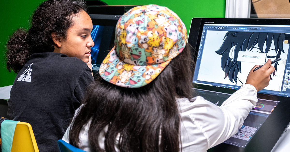 Two students working at a computer and pointing at a character drawing on the screen.