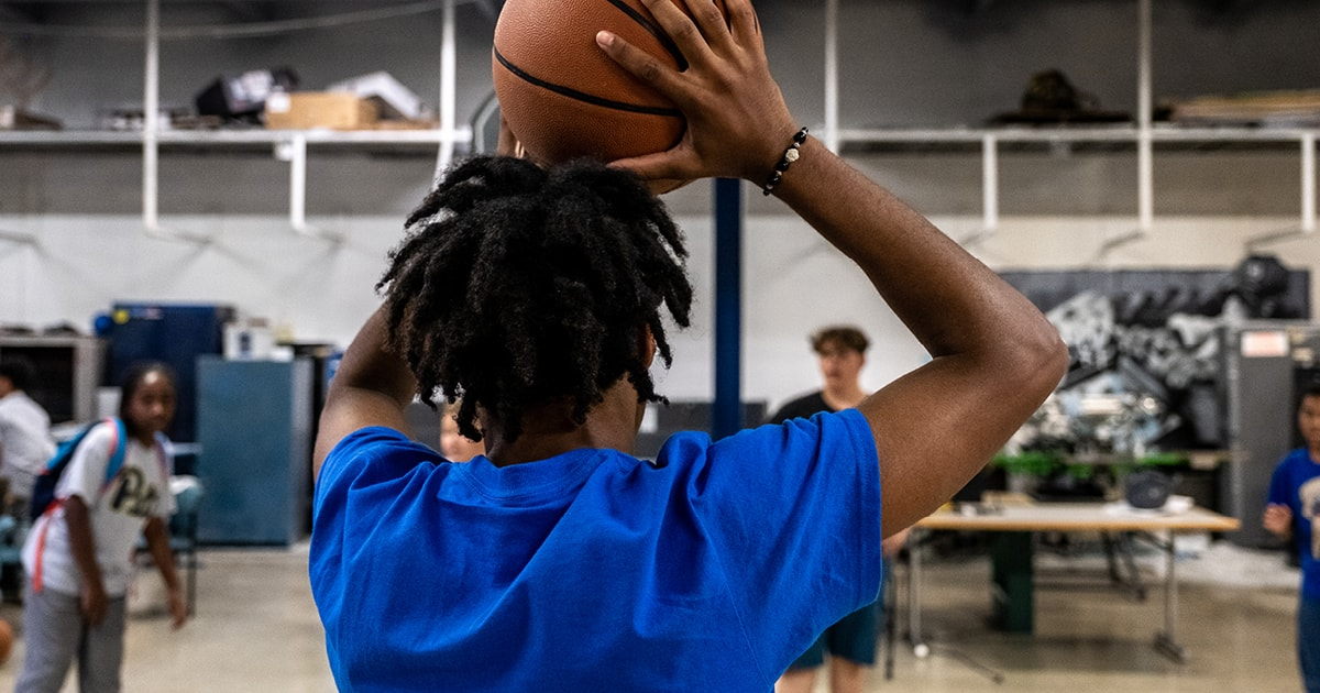 A student holds a basketball above their head.