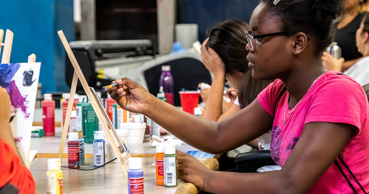 Students holds a paintbrush in front of a tabletop easily, while surrounded by paint bottles
