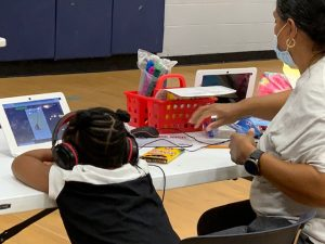 A girl wearing headphones looks at her virtual schoolwork in a gym, while an adult sits next to her.