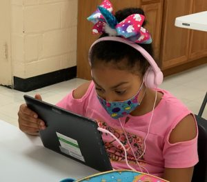 A girl wearing a hair bow, headphones and a masks looks at a screen while doing virtual schoolwork.